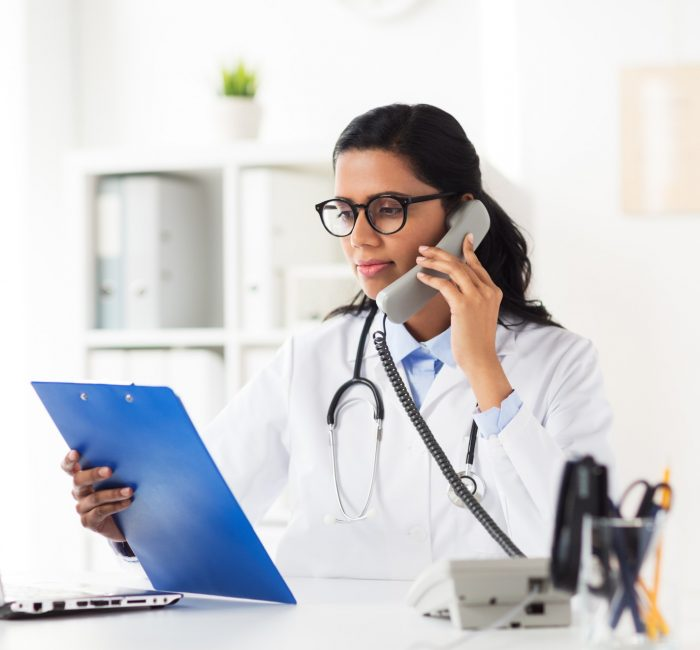 doctor-with-clipboard-calling-on-phone